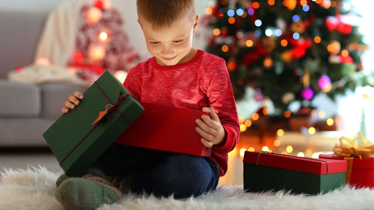 young boy smiling opening gift